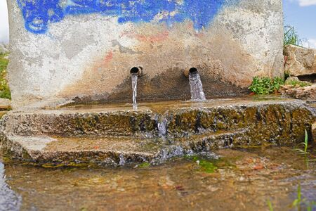 Historic fountain in an old village. Flowing natural spring water.