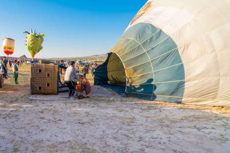 Cappadocia / Turkey - July 07 2019: Crew at sunset prepare hot air balloon for flight. Assembly and filling the balloon.