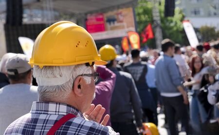 An unidentified old worker with yellow helmet joins May 1 Labor Day
