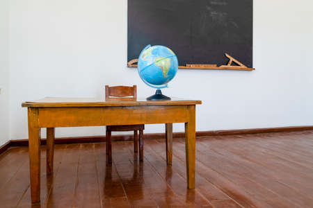 For the geography lesson, the globe stands on the teacher's desk. Tools and materials for math lesson stand on the chalkboard.
