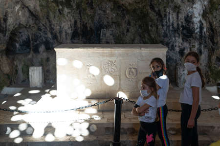 St. Pierre Church, Hatay/Turkey- September 13 2020: Light falling through the window of the dark church and young tourists visiting the church Editorial