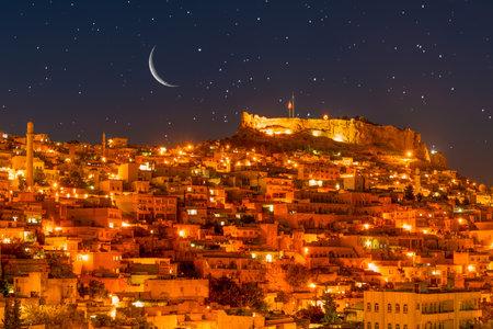 Ancient Mardin city at night under crescent and stars. Mardin night landscape.