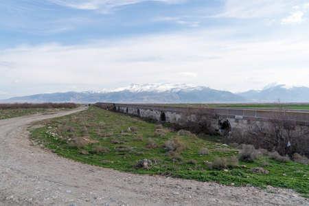 Bolvadin Kırkgoz Bridge was built in 1150 by the Byzantine Emperor Manuel Kommen. The bridge is 200 meters long. Sultan Mountains in background. Afyonkarahisar, Turkey 스톡 콘텐츠
