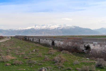 Bolvadin Kırkgoz Bridge was built in 1150 by the Byzantine Emperor Manuel Kommen. The bridge is 200 meters long. Sultan Mountains in background. Afyonkarahisar, Turkey