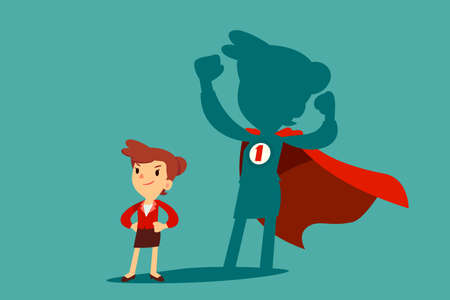 Confident businesswoman standing in front of her shadow wearing red cape as a superhero. Business ambition concept.