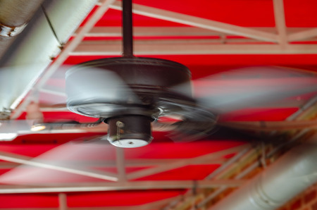 Outdoor ceiling fan under a red canopy