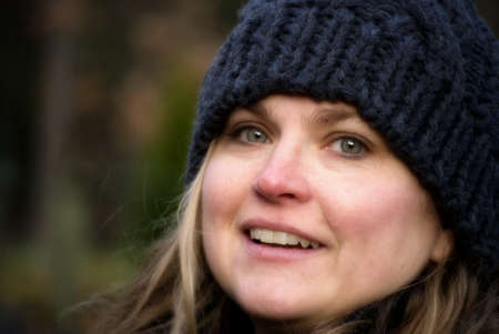 Woman in winter cap smiling and looking into camera an autumn day Stock Photo - 7591350