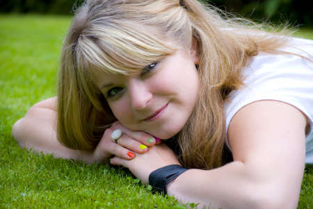 grass plot: Girl smiling and looking happy on a lawn Stock Photo