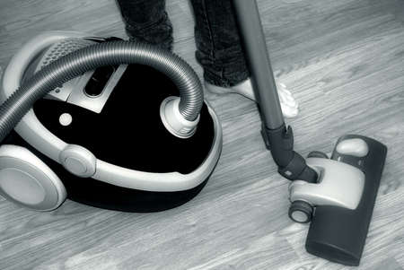 Barefoot female vacuum-cleaning, close-up in black and white photo