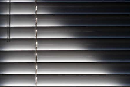 shining through: Suggestiva immagine della luce del sole che splende attraverso i ciechi Archivio Fotografico