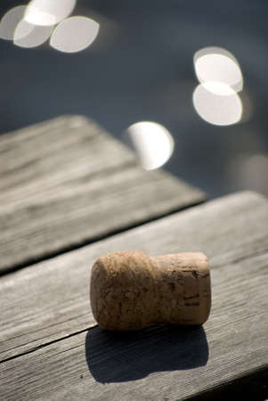 Wine cork on jetty, water with sun reflection in background Stock Photo - 10348066