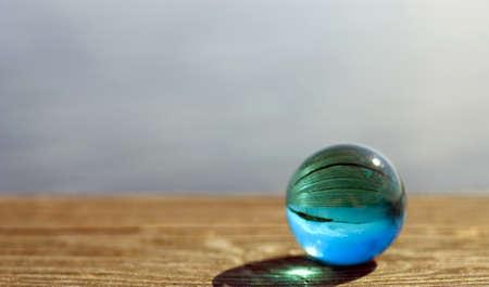 marbles close up: Beautiful summer coast seen through a blue glass ball