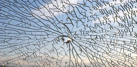 Broken glass,background of cracked window against blue sky photo