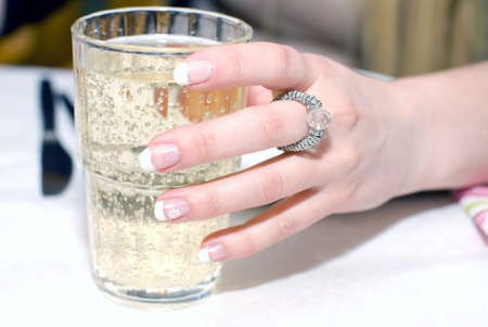 Close up of female hand, holding the glass with sparkling beverage Stock Photo - 13627967