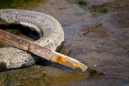 Debris in the form of old car tires and scrap metal in nature Stock Photo - 13628448