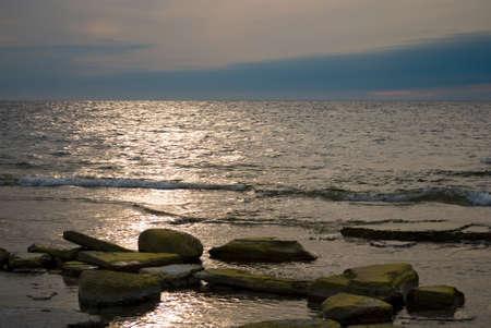 breaking wave: Rocks in warm summer water with beautiful sky Stock Photo