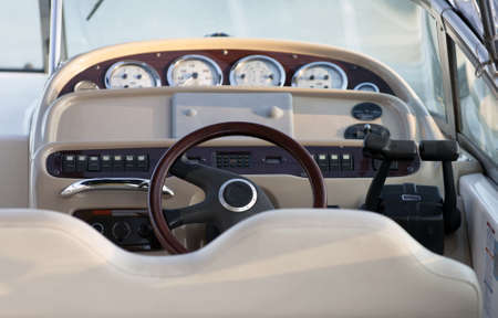 Exclusive boat controls, close up with focus on wooden steering wheel photo