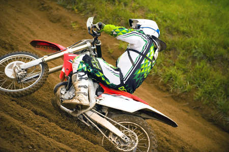 Close up of motocross driver going uphill in race photo