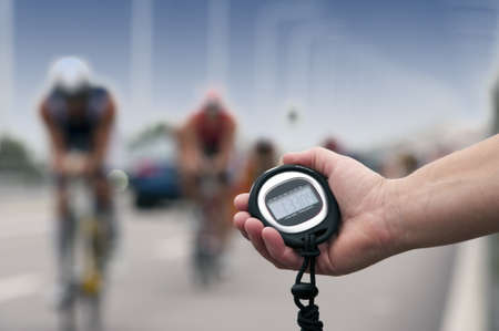 Timing of cyclists in bike race, close-up of hand and clock photo