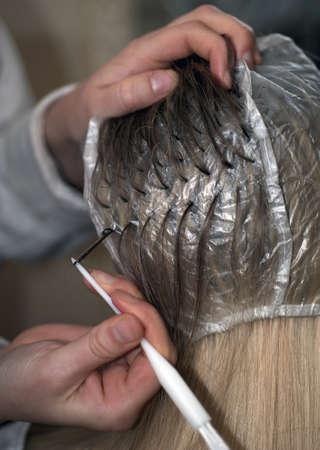 tinte cabello: La mujer se prepara para el teñido del cabello, close up con poca profundidad de campo