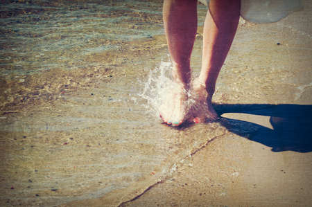 bare feet: Girl walking barefoot in the water, aged and worn vintage style photo