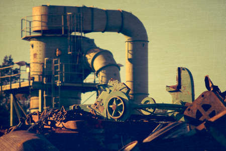 fragmentation: Machine behind the scrap heap works with fragmentation of the metal, aged and worn vintage style photo