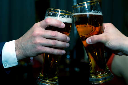 Two friends having a toast, beer glasses, close-up Stock Photo