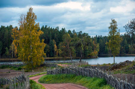 country roads: Dirt road and fence with autumn colored trees and the lake