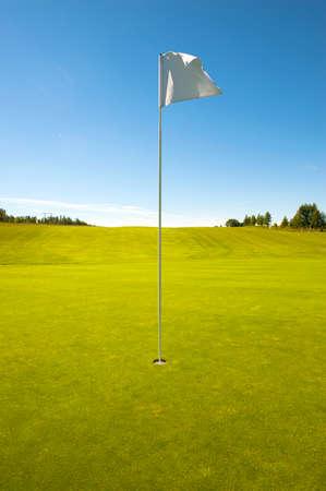 Golfgat met vlag, groen gebied en blauwe hemel Stockfoto