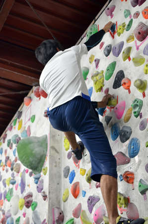 A Japanese man is climbing on practice wall indoors. View from back.