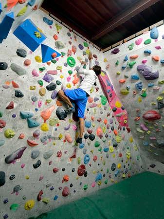 Een Japanse man klimt binnen op de oefenmuur. Uitzicht vanaf de achterkant. Stockfoto