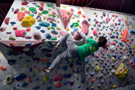 A Japanese man is climbing on practice wall indoors. View from side.