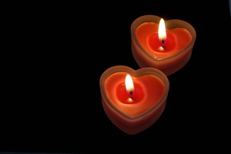 two read heart candles on black background photo