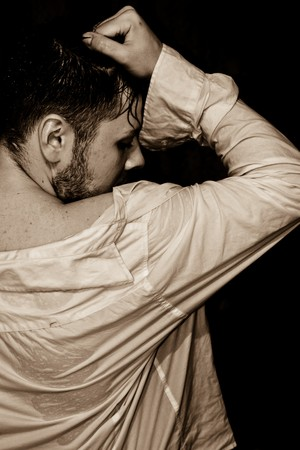 young man in a wet shirt on a black background photo
