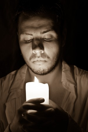 young man with a candle in hands photo