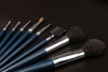 Make-up brushes on black background photo