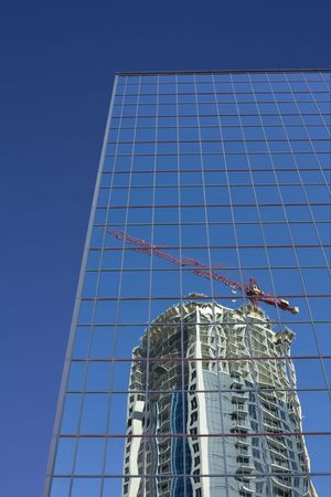 Crane and condo reflected in modern building Stock fotó