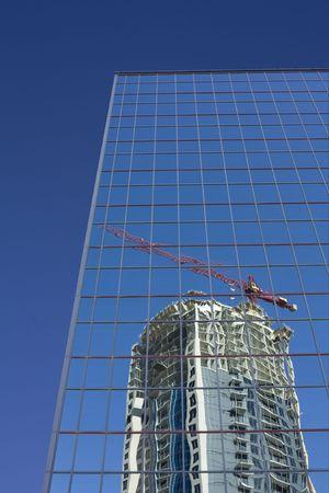 lattice window: Crane and condo reflected in modern building Stock Photo