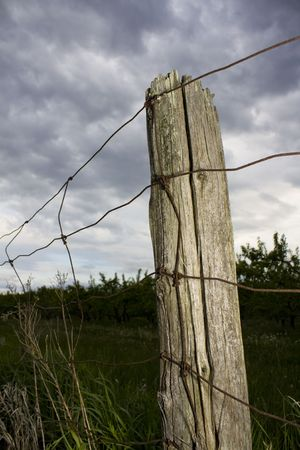 wire fence: Fence post under stormy sky