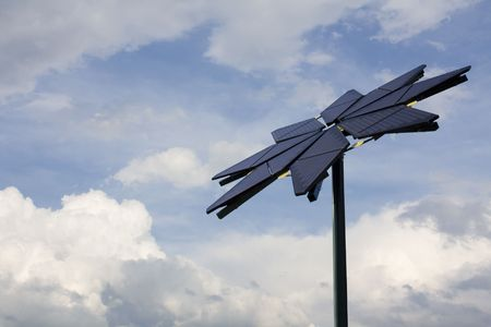 Flower shaped solar panel against backdrop of clouds