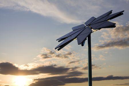 Flower shaped solar panel against backdrop of setting sun Stock fotó