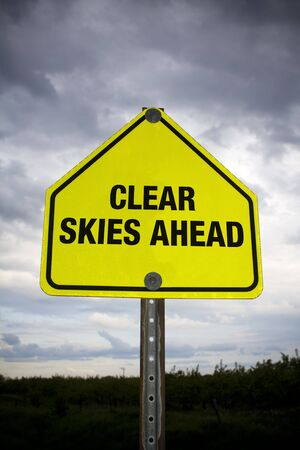 Clear skies ahead road sign against stormy sky
