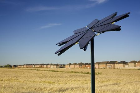 Flower shaped solar panel against backdrop of houses and farmers field Stock fotó