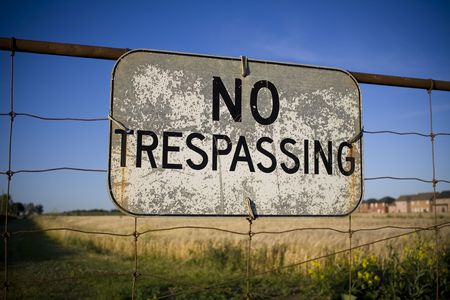 No trespassing sign against backdrop of houses encroaching on farm land. Urban sprawl concept.