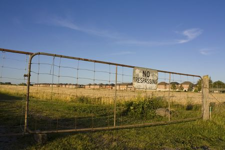 No trespassing sign against backdrop of houses encroaching on farm land. Urban sprawl concept. Stock Photo - 5328934