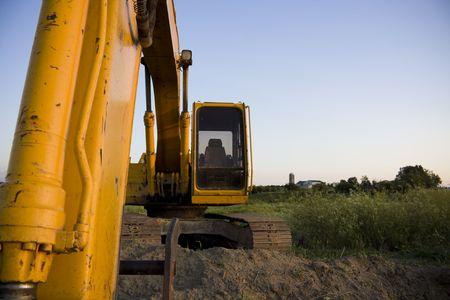 Excavator overlooking farmland shot at dusk
