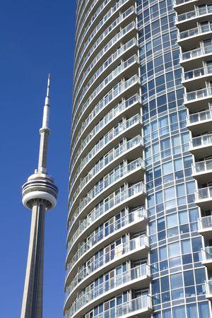 CN Tower beside condominium in toronto against clear blue sky