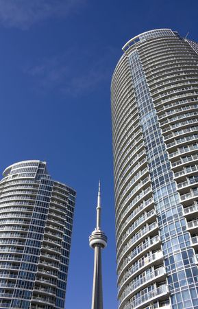 apartment living: CN Tower beside condominium in toronto against clear blue sky