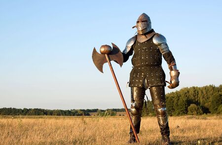 Medieval knight in the field with an axe Stock Photo - 5763358