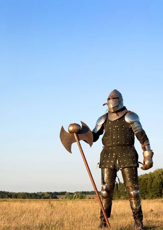Medieval knight in the field with an axe Stock Photo